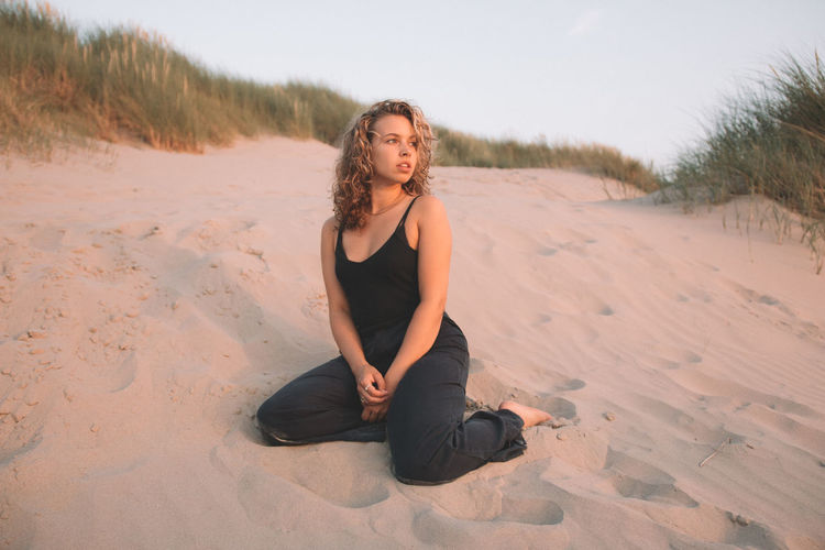 Young woman sitting on sand at beach against sky