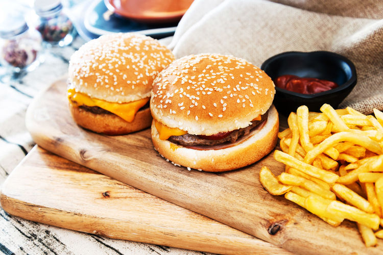 High Angle View Of Burger And French Fries On Cutting Board