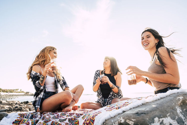 three young beauty women at the beach drinking a fruit juice Adventure Beach Beauty Blond Hair Casual Clothing Day Friendship Fun Group Of People Happiness Leisure Activity Lifestyles Nature Outdoors Real People Sea Sitting Sky Smiling Summer Sunlight Togetherness Vacations Young Adult Young Women