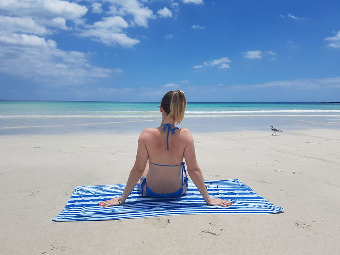 Rear View Of Woman Wearing Bikini While Sitting On Picnic Blanket At Beach During Summer