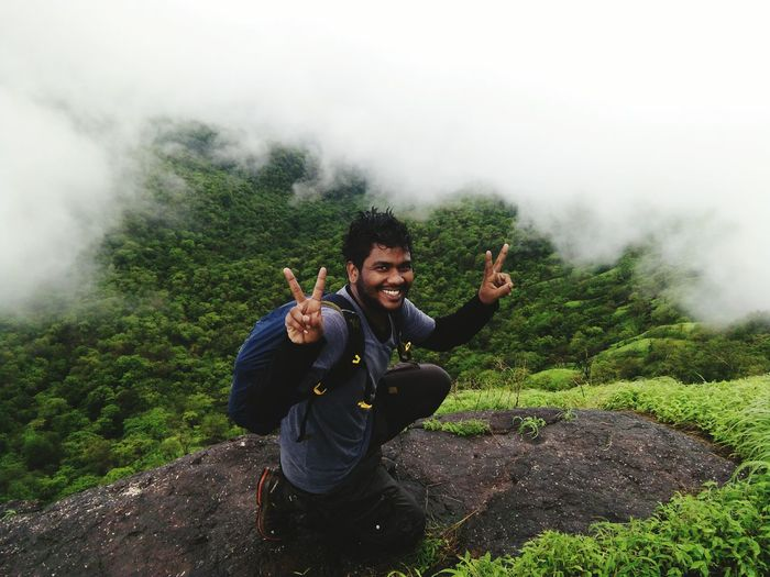 Portrait of man gesturing peace sign on mountain