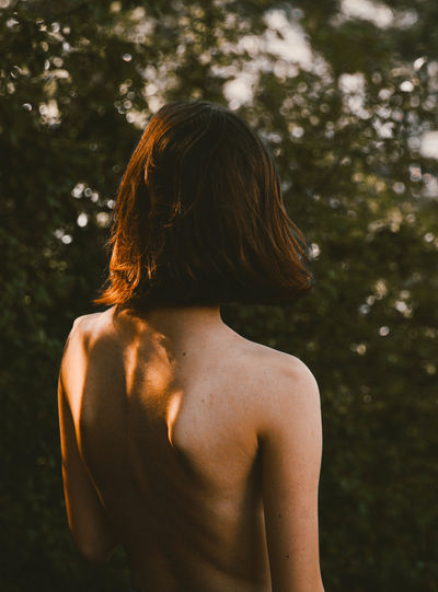 Rear View Of Shirtless Young Woman Standing In Forest