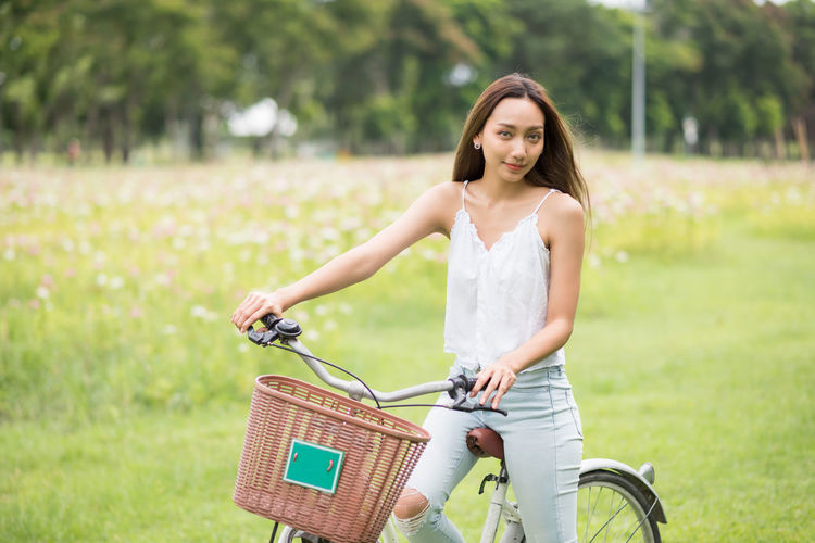 Portrait of smiling young woman with bicycle on basket