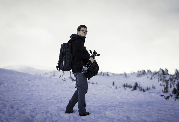 Mature man with backpack and tripod standing on snow
