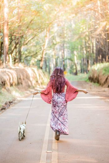 Rear view full length of woman in long dress walking with dog on road