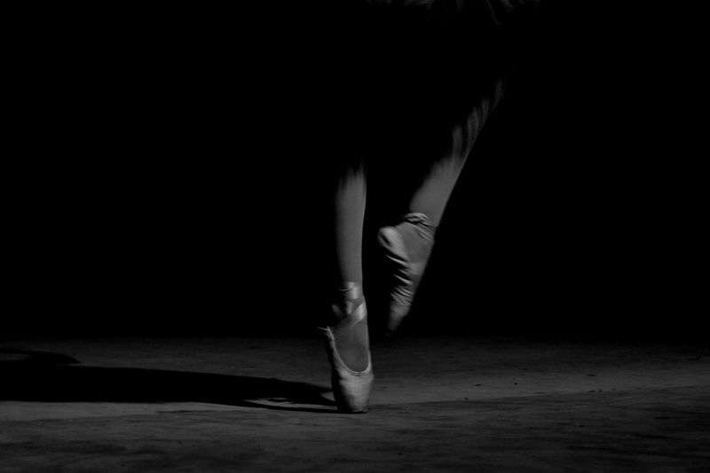 Low Section Of Woman Dancing Against Black Background