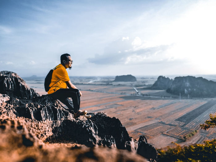 Side View Of Man Sitting On Rock Against Sky
