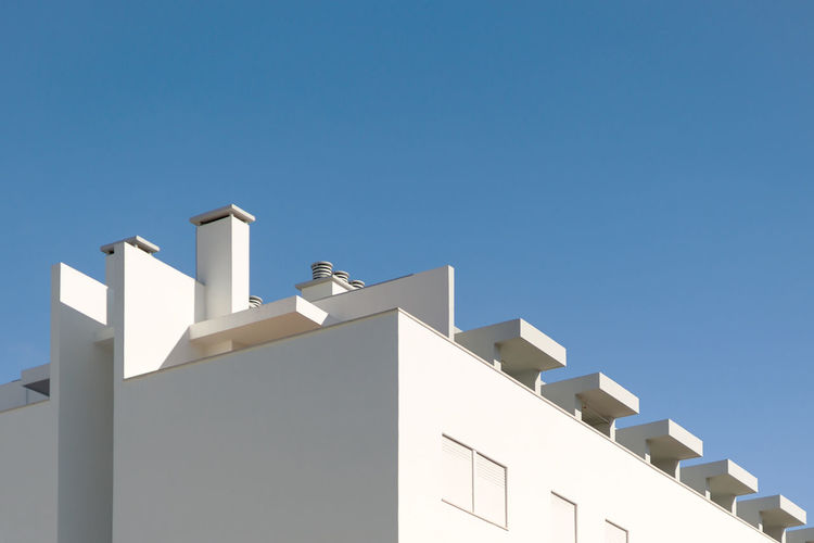 Low angle view of white building against clear blue sky