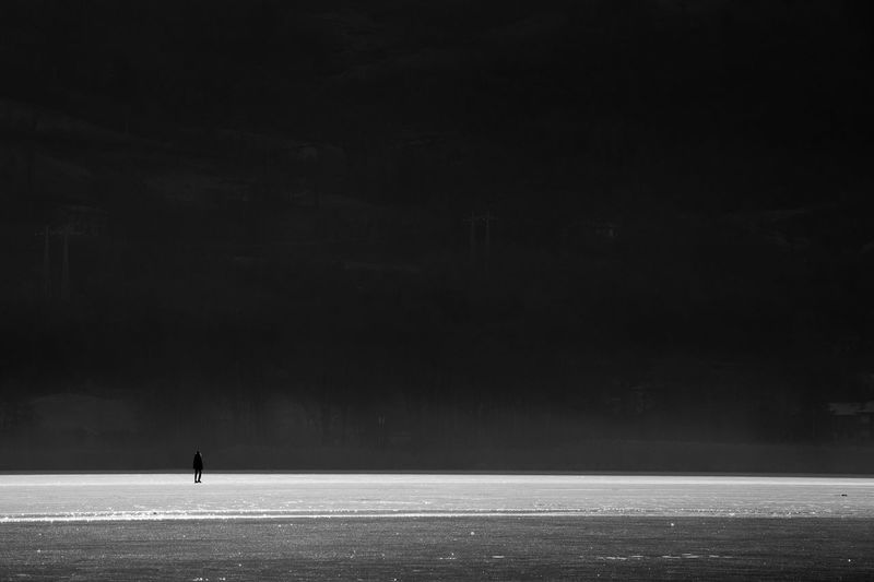 Silhouette man on snowy field during winter