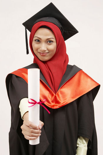 Young Woman In Graduation Gown Standing Against White Background