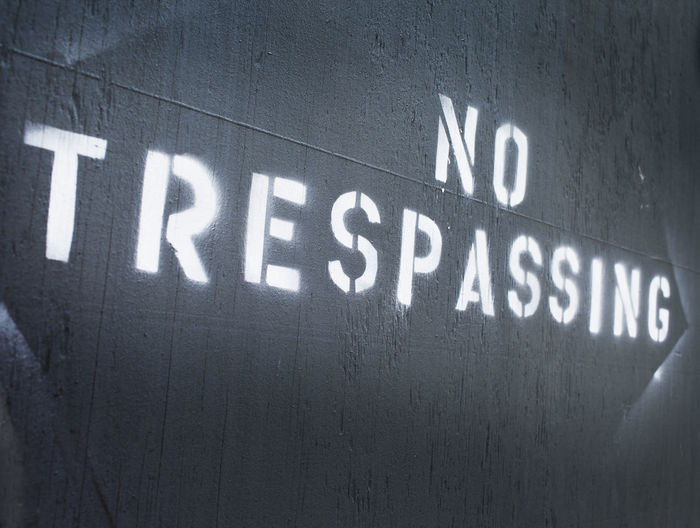 No trespassing spray painted on a wall. Communication Forbidden Lettered No People No Trespassing Painted Prohibited Sign Stencil Text White
