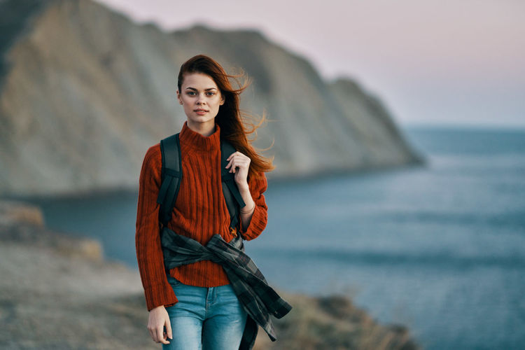 Portrait of beautiful young woman standing in sea