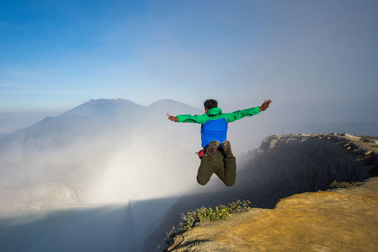 INDONESIA Travel Adventure Arms Outstretched Arms Raised Beauty In Nature Blue Sky Carefree Day Enjoyment Freedom Full Length Human Arm Jumping Kawah Ijen Leisure Activity Lifestyles Limb Men Mid-air Mountain Nature One Person Outdoors Real People Sky Sport Tourism Vitality