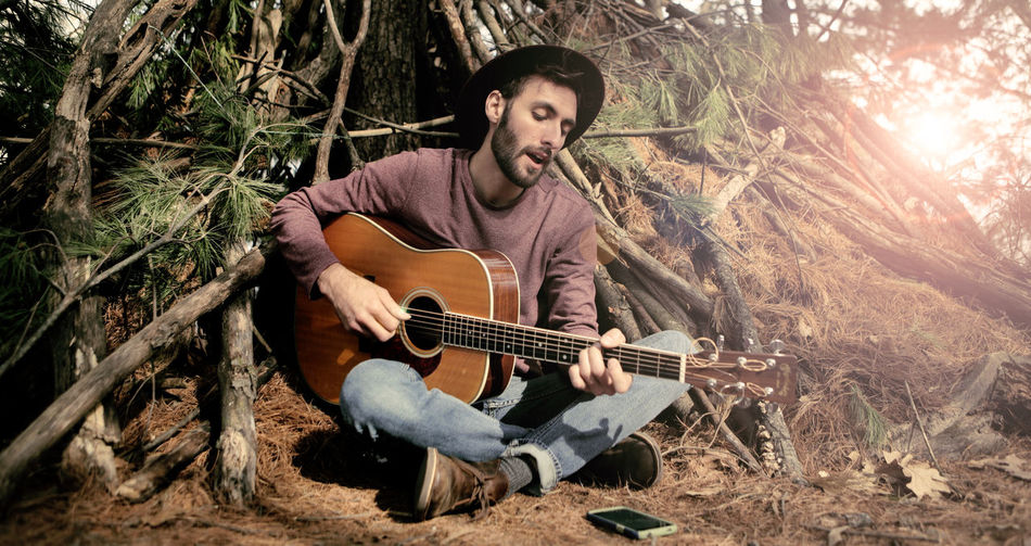 Man Playing Guitar In Forest