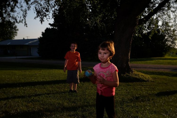 Siblings Playing On Grassy Field Against Trees At Yard