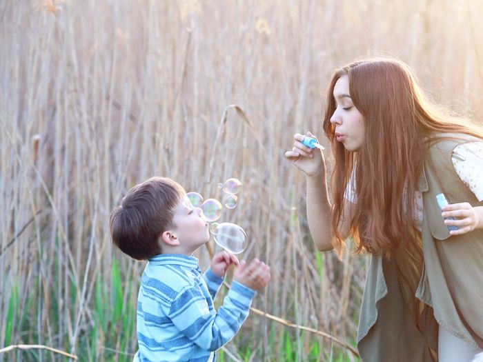 playing with blowing bubbles Teenager Playtime Playing Soap Bubbles Family Fun Family Life Sunshine Blowing Bubbles Blowing Childhood Child Offspring Leisure Activity Togetherness Women Casual Clothing Girls Boys Nature Holding Family Bonding Enjoyment Innocence Day