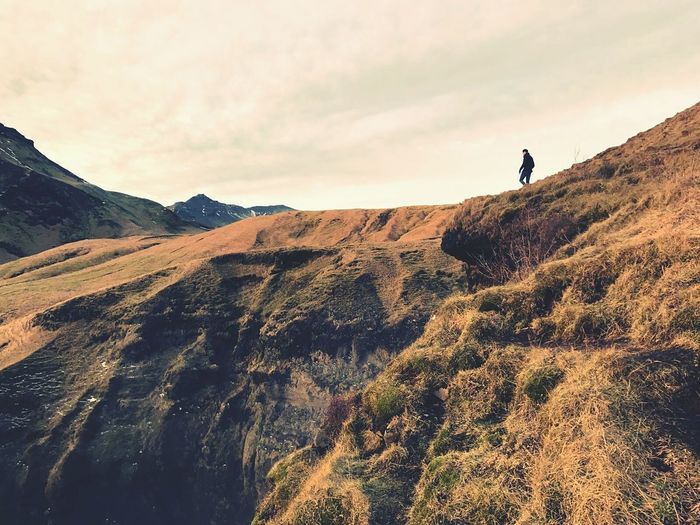Low angle view of man hiking on mountain against sky
