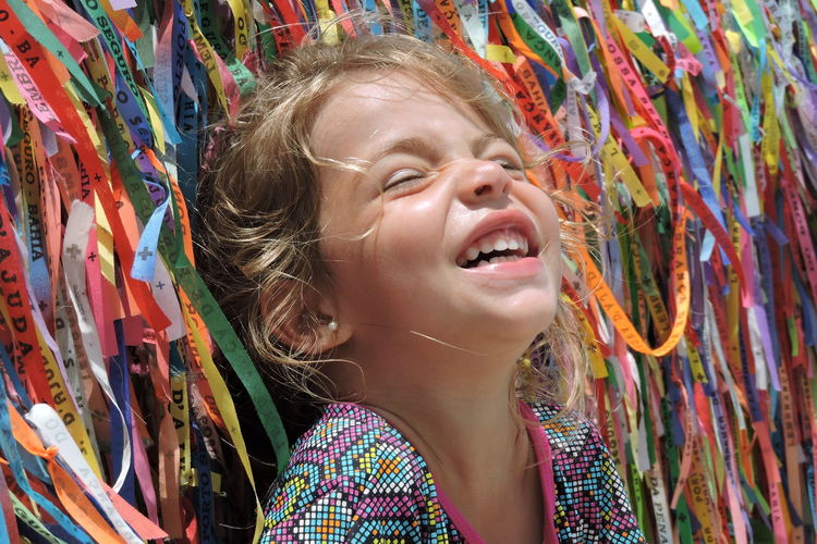 Close-up of happy girl against multi colored ribbons