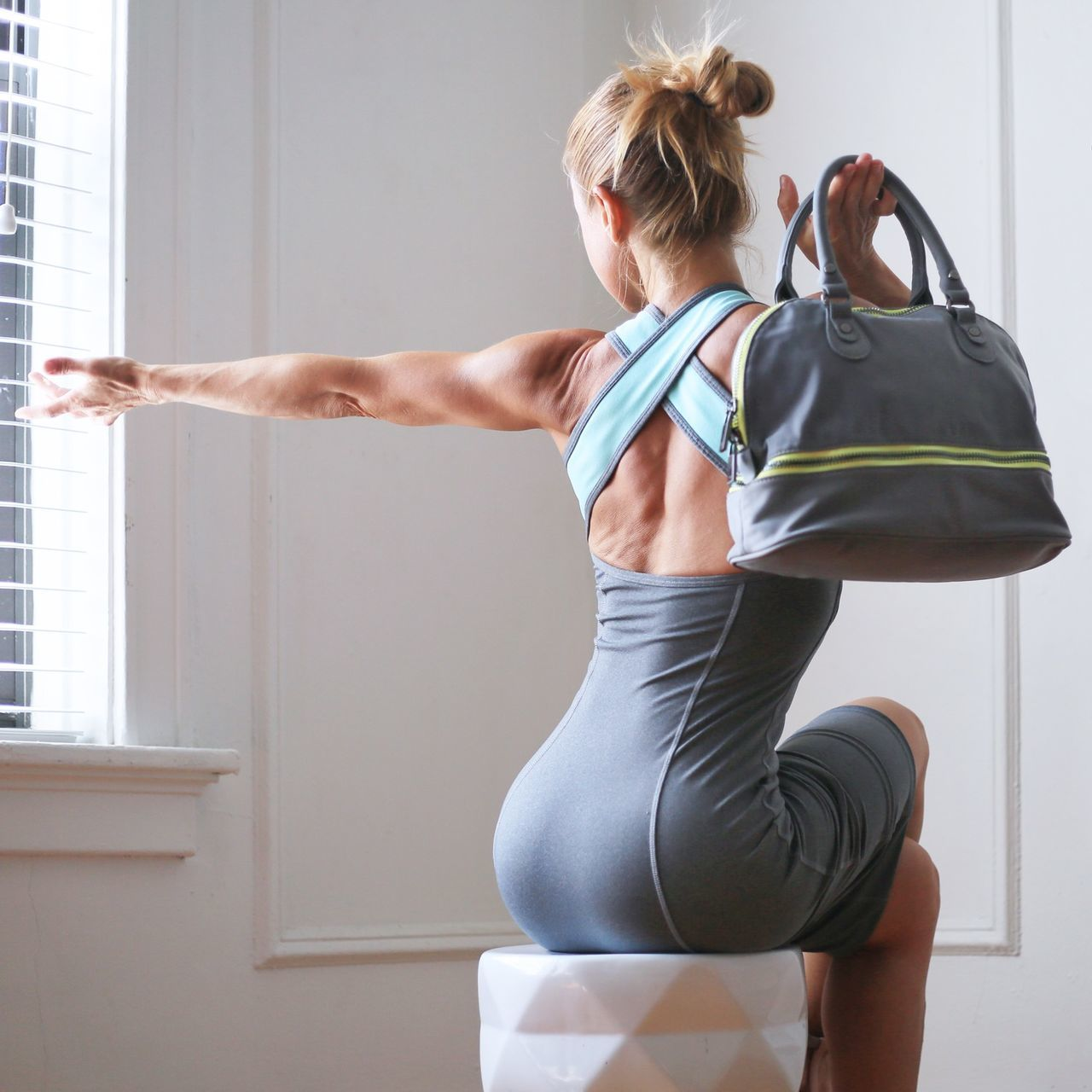 Rear view of athlete woman stretching while holding shoulder bag at home