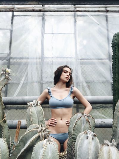 Young model wearing lingerie while standing in greenhouse