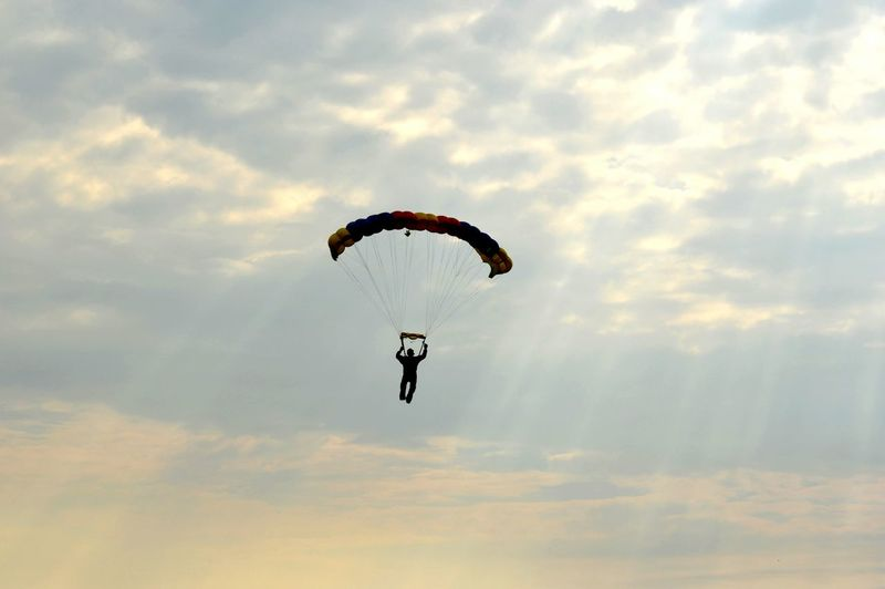Person Paragliding Against Cloudy Sky