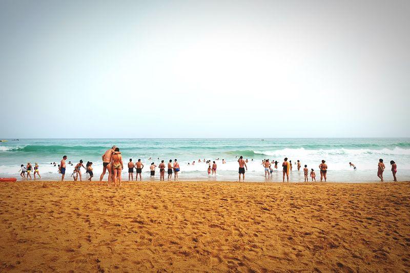 People Enjoying At Praia Do Tunel Beach Against Sky