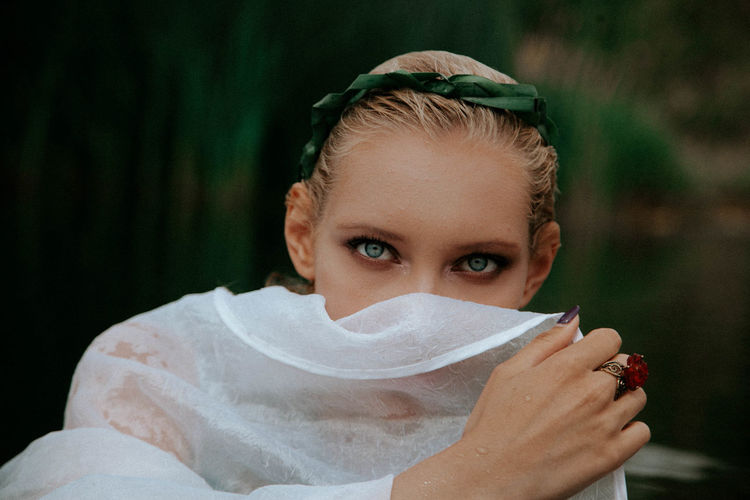 Close-up portrait of beautiful woman covering face with scarf