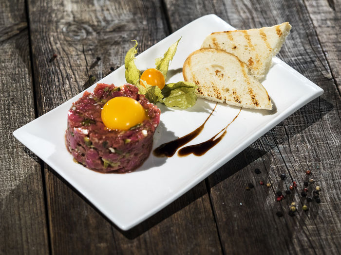Raw steak tatar with egg yolk Bread Close-up Day Egg Food Food And Drink Freshness Healthy Eating Indoors  Indulgence Meat No People Plate Raw Ready-to-eat SLICE Steak Table Tatar Wood - Material Yolk