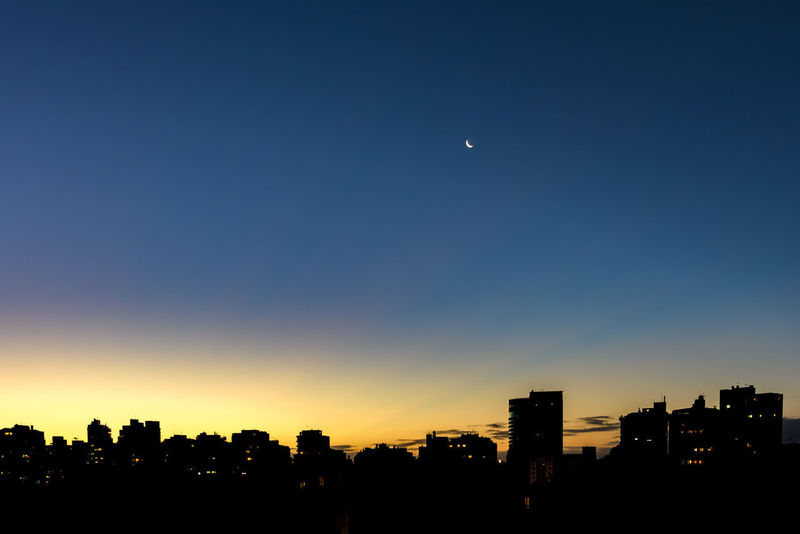 Skyline of dusk in the summer of the city of Porto Alegre in Rio Grande do Sul with the moon in the sky of vibrant colors Brazil Night Shot Porto Alegre Architecture Building Exterior Built Structure City Cityscape Clear Sky Dusk Half Moon Metropolis Moon Nature Night No People Outdoors Rio Grande Do Sul  Scenics Silhouette Sky Skyscraper Summer Sunset Urban