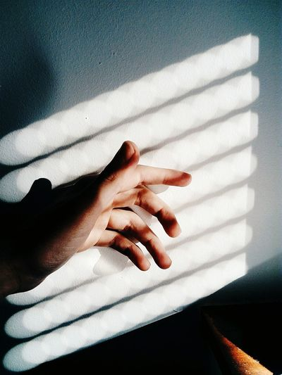High angle view of sunlight falling on hand by wall