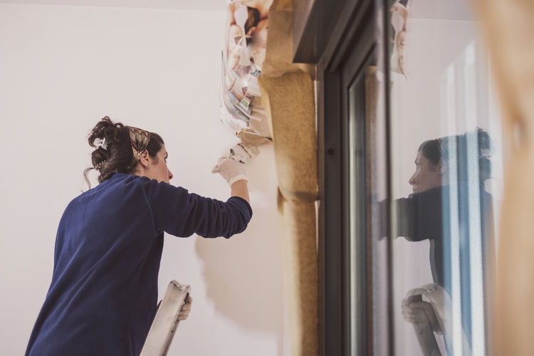 Side view of woman painting wall at home