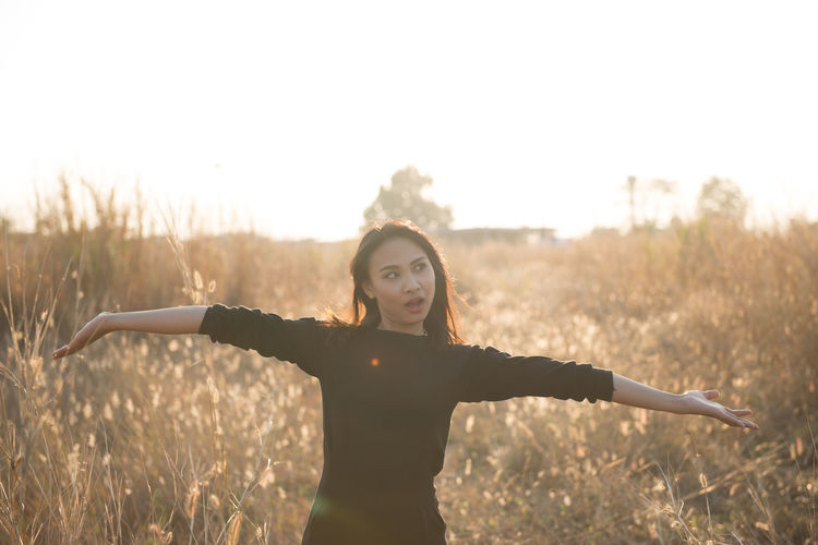 Woman With Arms Outstretched Standing On Field