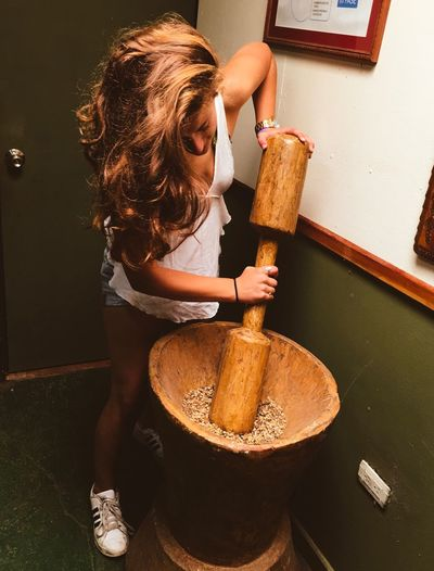 Young woman grinding ingredients using large mortar and pestle against wall