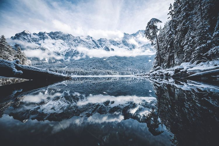 Scenic view of calm lake by snow covered mountains against sky