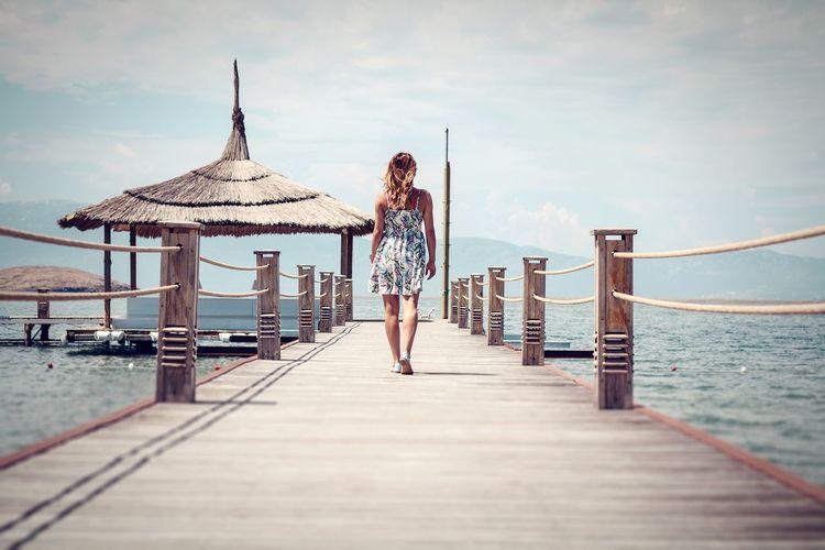 Woman Walking On Pier By Sea Against Sky