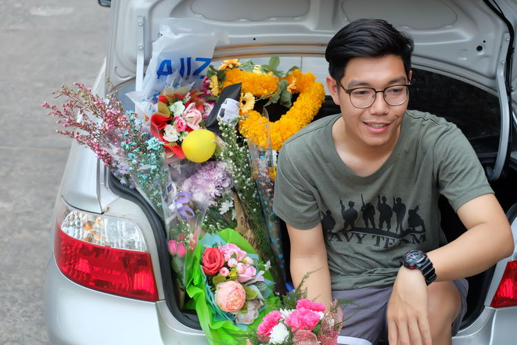 Smiling young man selling bouquets in car trunk