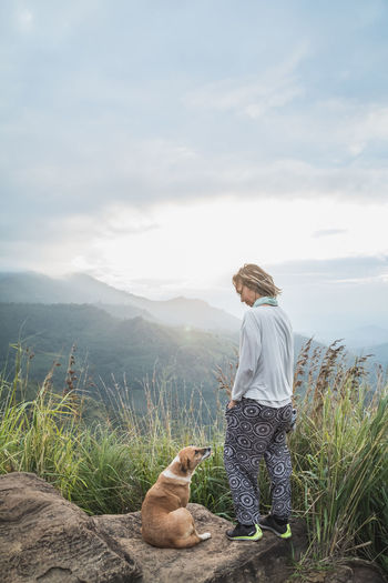 Woman with dog standing on mountain against sky