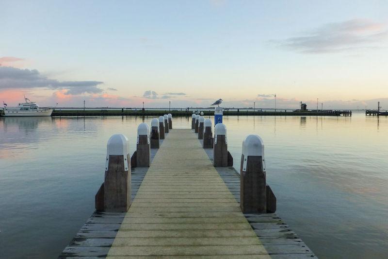 Boardwalk over sea against sky at sunset