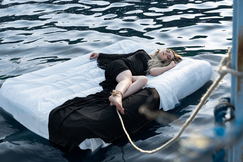 High angle view of woman sleeping on pool raft in lake