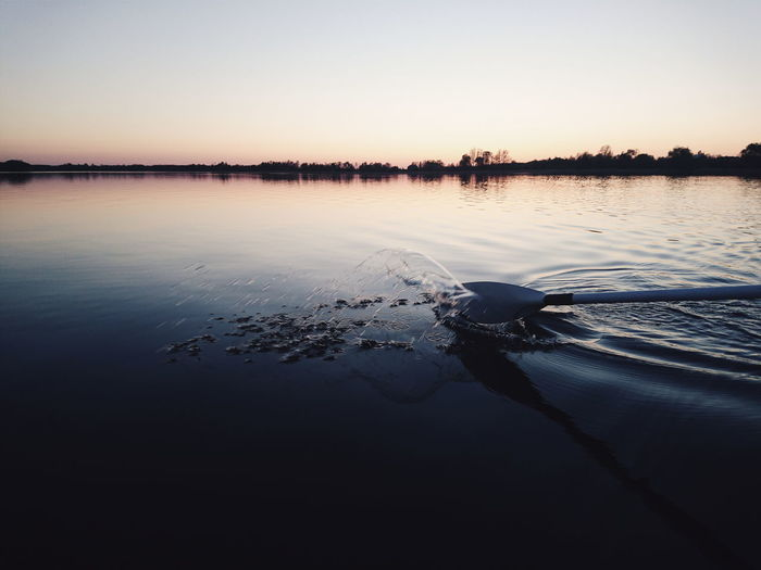 Oar Splashing Water In Sea Against Clear Sky During Sunset