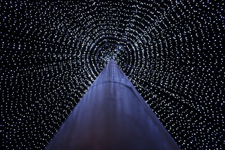 Low angle view of illuminated ceiling against sky at night