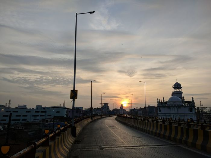Highway amidst buildings in city during sunset