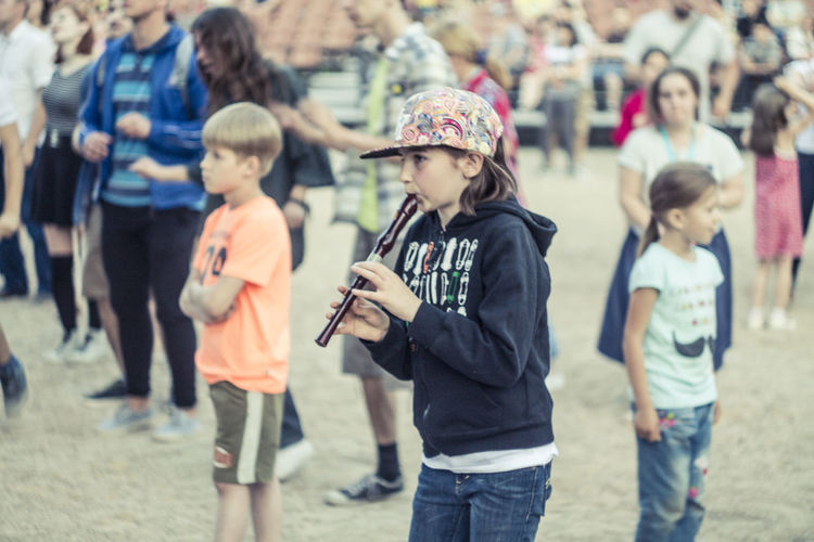 Girl playing flute while standing against crowd