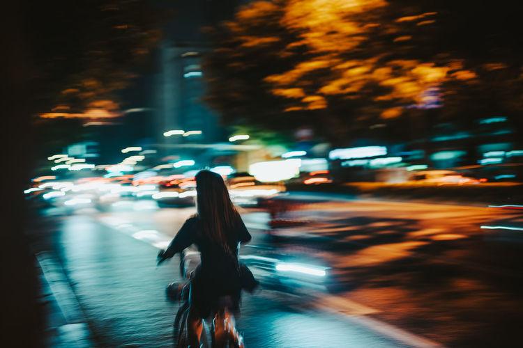 Woman walking on illuminated street at night