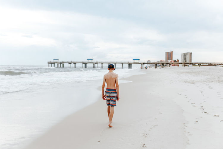 Rear view of teenage boy walking on beach