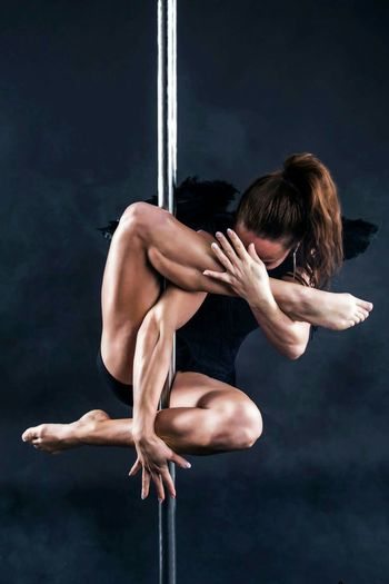 Woman Hanging From Pole