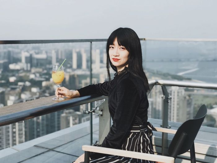Portrait of young woman with drink sitting in balcony against cityscape
