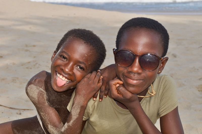 Portrait of happy boy with girl on beach