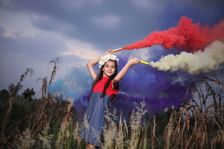 Portrait of smiling cute girl holding distress flares while standing against sky at dusk