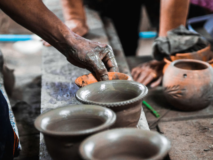 Cropped hand of man making pottery in workshop